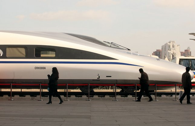 Visitors look at China's homegrown bullet train, the CRH380A, the train that set an operating speed record of 302 miles per hour during a test run on the Beijing-Shanghai line last week, on display outside the venue for the 7th World Congress on High Speed Rail in Beijing December 8, 2010. China now leads the world with 4,680 miles of high-speed rail network, and thousands of miles of new high-speed railways are under construction nationwide. UPI/Stephen Shaver