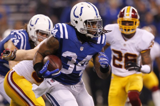 Indianapolis Colts running back Trent Richardson (34) fights to break free from Washington Redskins' Trent Murphy (93) during the first half of play at Lucas Oil Stadium in Indianapolis, Indiana, November 30, 2014. UPI/John Sommers II