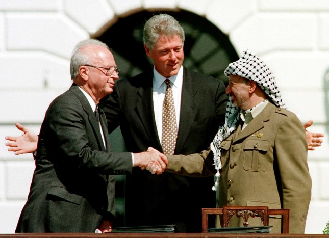 Then U.S. President Bill Clinton looks on as Israeli Prime Minister Yirzhak Rabin and Palestinian Liberation Organization chief Yasser Arafat exchange handshakes after signing the Arab-Israeli Peace Treaty on Sept. 13, 1993, in a ceremony at the White House. File Photo by Leighton Mark/UPI