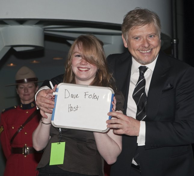 Comedian Dave Foley the show host helps volunteer Laura hold up his name board upon arriving on the Red Carpet for the 2009 Genie Awards at the Canada Aviation Museum in Ottawa the Capital of Canada, April 4, 2009. The Genie Awards are Canada's version of the Oscars. (UPI Photo/Heinz Ruckemann)