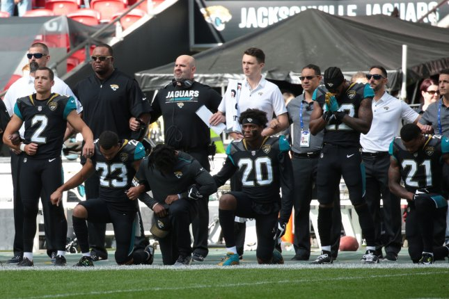 Jacksonville Jaguars team members crouch down and kneel during the American National anthem in defiance of President Trump remarks in the NFL International Series match against the Baltimore Ravens on Sunday at Wembley Stadium in London, England. Photo by Hugo Philpott/UPI