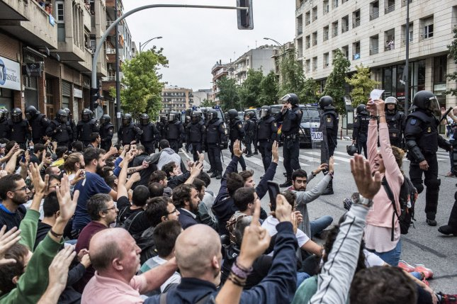 Spanish National Police officers prevent people from entering a polling station in Barcelona on Sunday for a referendum on independence for Catalonia. The central government in Madrid has banned the vote. Photo by Angel Garcia/ UPI