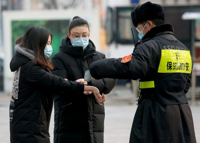 A security guard checks the temperature of people visiting a popular shopping mall due to the threat of the deadly COVID-19 spreading in Beijing on Monday. Photo by Stephen Shaver/UPI