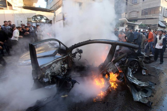 Palestinian firefighters extinguish fire from the car of Ahmad Jaabari, head of the military wing of the Hamas movement, the Ezzedin Qassam Brigades, after it was hit by an Israeli air strike in Gaza City on November 14, 2012. On July 19, 2015, a series of bombs destroyed cars belonging to Hamas and Islamic Jihad officials in Gaza's Sheikh Radwan neighborhood, which is considered a Hamas stronghold. One Hamas commander blamed the Sunni militant group known as the Islamic State. File photo by Ashraf Mohammad/UPI