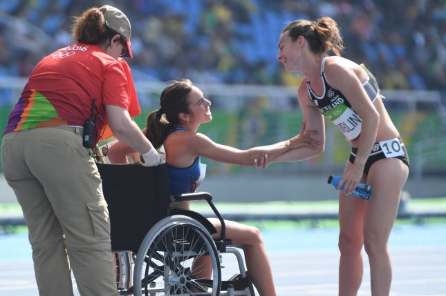 New Zealand's Nikki Hamblin (R) clasps arms with USA's Abbey D'Agostino as she is wheeled from the finish line after the second heat of the Women's 5000m at the 2016 Rio Summer Olympics in Rio de Janeiro on Tuesday. Photo by Terry Schmitt/UPI