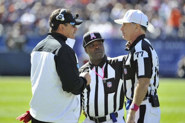 Carolina Panthers head coach Ron Rivera (L) talks with former NFL referee Terry McAulay (77) and side judge Michael Banks (C) during the second quarter against the Chicago Bears on October 2, 2011 at Soldier Field in Chicago. File photo by Brian Kersey/UPI