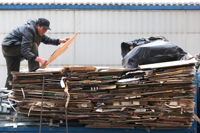 A Chinese trash collector stacks cardboard boxes on the back of his truck at a recycling drop-off site in Beijing. File Photo by Stephen Shaver/UPI