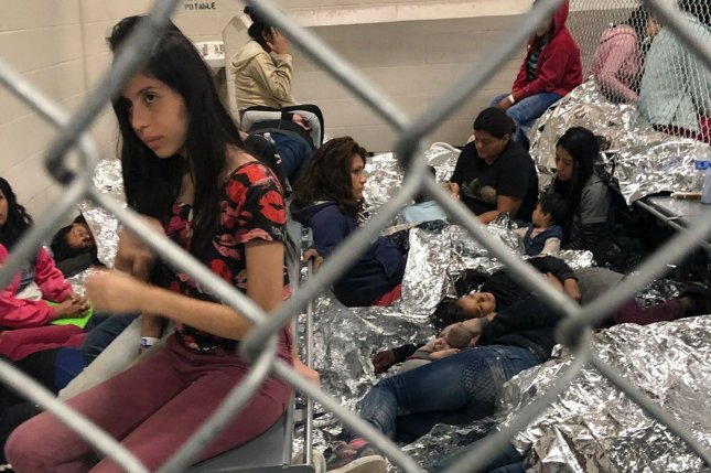 Women and children lie on the floor amid space blankets and behind cyclone fencing at the Central Processing Center in McAllen, Texas on July 13. File Photo courtesy of U.S. Rep. Doris Matsui's office