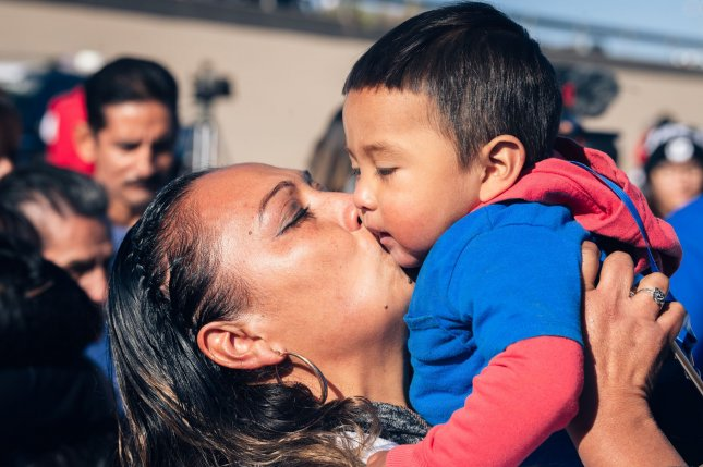 Separated migrant families embrace in the Rio Grande between El Paso, Texas, and Ciudad Juarez, Chihuahua, Mexico, on October 26, 2019. File Photo by Justin Hamel/UPI