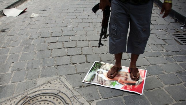 A Syrian rebel fighter stands on a picture of Syrian President Bashar al-Assad, in the Old Town of Aleppo, Syria, September 12, 2012. UPI/Ahmad Deeb