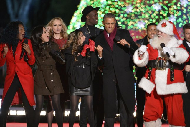 U.S. President Barack Obama (C) dances with Santa Claus as he joins performers at the conclusion of the National Christmas Tree Lighting Ceremony, December 4, 2014, in Washington, DC. The tradition was started in 19233 by President Calvin Coolidge and traditionally begins the Holiday Season in the Capital. UPI/Mike Theiler
