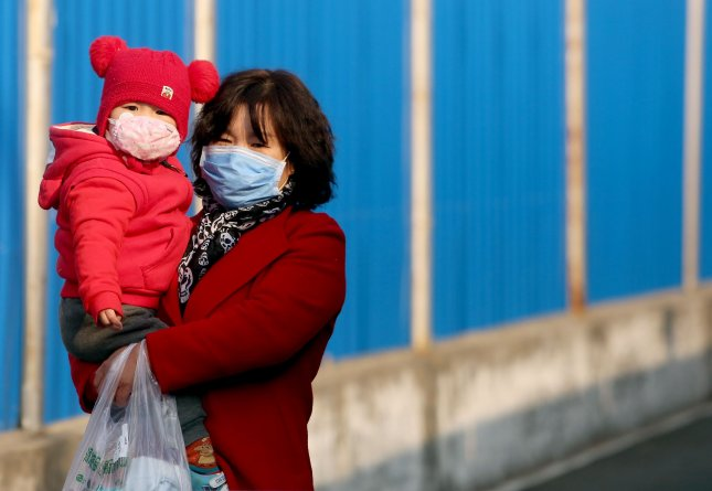 A mother carries her daughter on an empty street in Beijing on Monday. Photo by Stephen Shaver/UPI