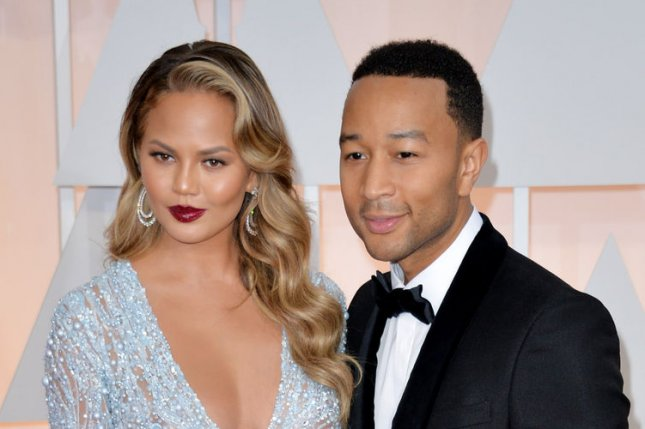 Chrissy Teigen (L) and husband John Legend at the 87th Academy Awards on February 22, 2015. Photo by Kevin Dietsch/UPI