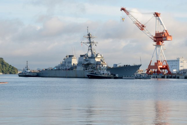 Tugboats assist the USS Fitzgerald as it moves toward dry dock in Yokosuka on Tuesday to continue repairs and assess damage sustained from its June 17 collision with a merchant vessel. Photo by MC1 Peter Burghart/U.S. Navy/UPI
