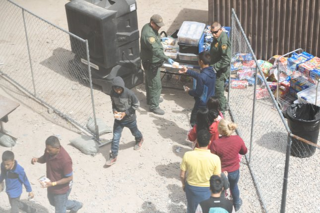 Customs and Border Patrol pass out snacks to apprehended migrants as they wait to be processed at the Paso del Norte Port of Entry in El Paso, Texas on March 22. Border Patrol detention centers have soared past capacity, prompting the mass release of migrants. Photo by Justin Hamel/UPI