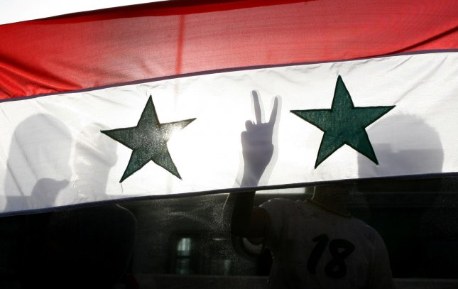 A Syrian protester gestures victory signs behind their national flag as they shout slogans calling for Syria's President Bashar al-Assad to step down. Unable to travel, residents of the Golan Heights must show their support in other ways. UPI
