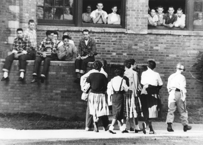 White students watch from windows and steps of Little Rock Central High School on October 16, 1957, as six black students are escorted to morning classes. President Dwight Eisenhower was compelled to enforce the Supreme Court's public school desegregation decision with troops after the integrity of the court was challenged by Arkansas Gov. Orval Faubus. UPI File Photo