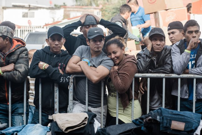 Migrants who traveled from Central America wait in line in front of a shelter in Tijuana, Mexico on December 23, 2018. File Photo by Ariana Drehsler/UPI