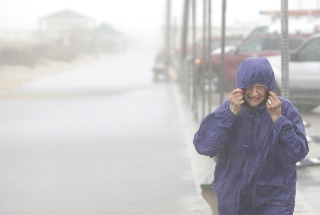A woman holds on to her hood when rain and wind arrive on the east coast of the United States on October 2, 2015 in Seaside Heights, N.J. Two people died in storms in Maryland and New Jersey on Tuesday. File Photo by John Angelillo/UPI