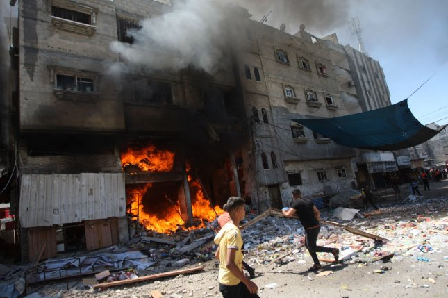 Palestinians battle a blaze following an Israeli strike on a house in Rafah in the southern Gaza Strip on Saturday. Photo by Ismael Mohamad/UPI