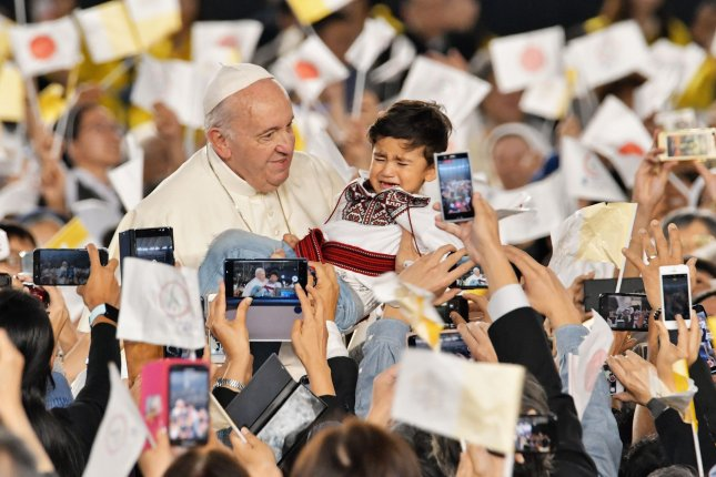 Pope Francis caresses a child as he arrives for holy mass Monday at the Tokyo Dome in Tokyo, Japan. Photo by Keizo Mori/UPI