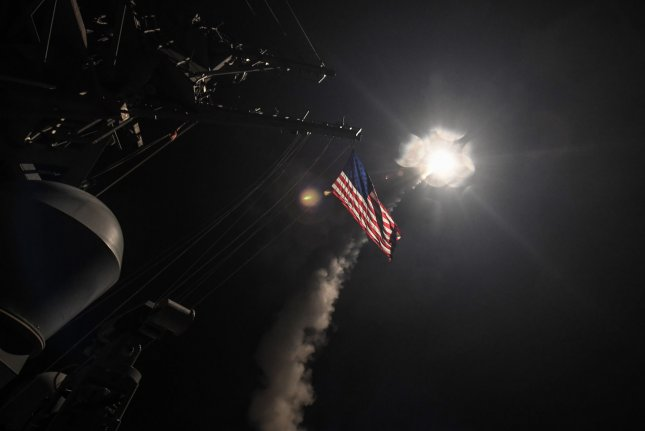 A cruise missile illuminates the American flag on the U.S. Navy's guided-missile destroyer USS Porter in the Mediterranean Sea on April 7, 2017. AFRICOM on Monday said two civilians were killed a year ago in Somalia by a U.S. airstrike. File Photo by MCS 3rd Class Ford Williams/U.S. Navy/UPI