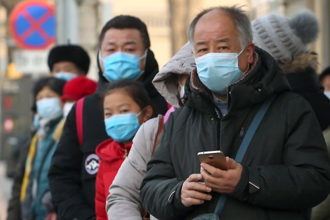 Chinese wear face masks while waiting for a bus in Beijing on January 4. World Health Organization experts will arrive in the country Thursday to trace the origins of the coronavirus pandemic. File photo by Stephen Shaver/UPI