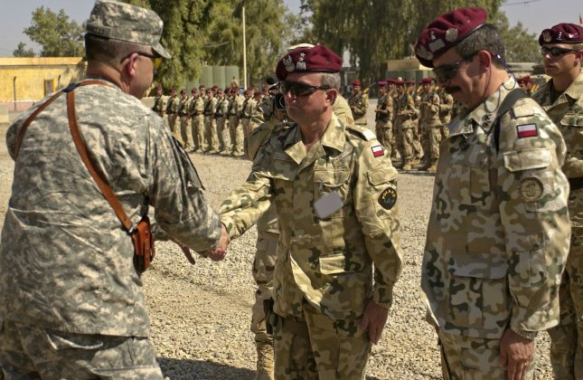 U.S. Army Lt. Gen. Peter Chiarelli Multinational Corps-Iraq Commander congratulates incoming Multinational Division-Central South (MND-CS) Commander Polish Army Maj. Gen. Bronislaw Kwiatkowski after he accepted command of the MND-CS during the Multinational Division Central South Change of Command Ceremony at Camp Echo, Iraq, on Tuesday, July 18, 2006. U.S. Army Lt. Gen Peter Chiarelli Multinational Corps - Iraq Commander officiated the ceremony where Polish Army Maj. Gen. Edward Gruszka relinquished command to Polish Army Maj. Gen. Bronislaw Kwiatkowski. (UPI Photo/Adrian Cadiz/USAF)