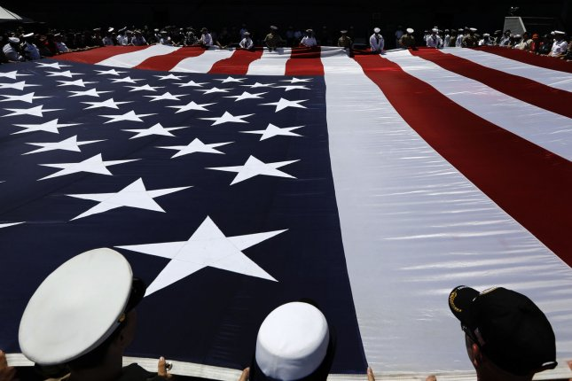 U.S. servicemen and women unfurl a 100-foot American flag during Memorial Day ceremonies at the Intrepid Sea Air & Space Museum in New York City on May 27. File Photo by Peter Foley/UPI