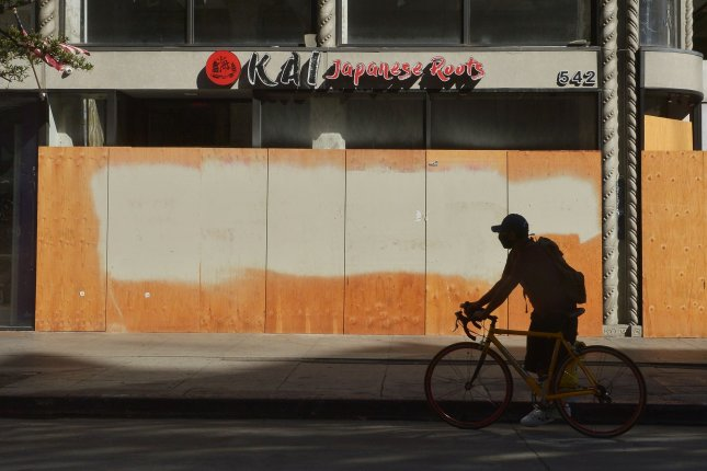A bicyclist passes a closed restaurant in downtown Los Angeles, Calif., on August 10 after it was boarded up as a result of the coronavirus pandemic. File Photo by Jim Ruymen/UPI