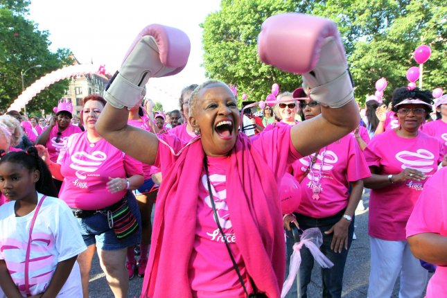 A breast cancer survivor dances and celebrates with boxing gloves on before the start of the annual Koman Race for the Cure in St. Louis on June 14, 2014. When a survivor of early stage breast cancer takes up healthy eating and regular exercise, the odds of the disease returning go down, according to a study. UPI/Bill Greenblatt