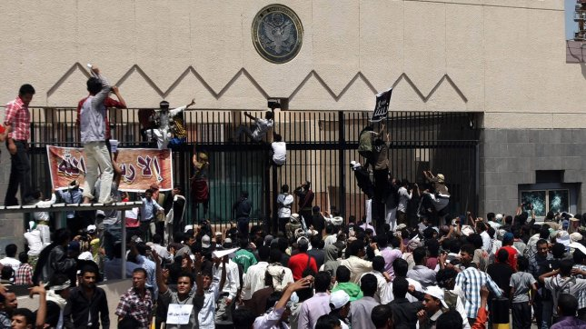 Protesters climb a fence at the United States embassy in Sanaa in Yemen September 13, 2012. The State Department ordered non-emergency U.S. government personnel evacuated from Yemen on Monday due to the continued potential for terrorist attacks. UPI/Mohammad Abdullah