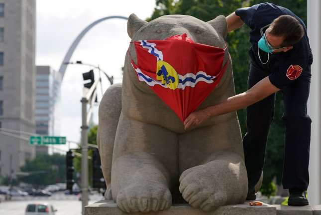 A firefighter adjusts a mask on a bear sculpture in front of Stifel Theater on Thursday in St. Louis, Mo. The fire department is helping the St. Louis Arts Chamber of Commerce install symbolic face coverings on statues to promote mask use. Photo by Bill Greenblatt/UPI