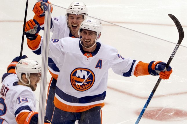 New York Islanders right wing Josh Bailey (L) celebrates his game-winning goal with center Brock Nelson (C) in the second overtime period of Game 5 against the Pittsburgh Penguins in the opening round of the NHL Stanley Cup Playoffs series Monday at PPG Paints Arena in Pittsburgh. Photo by Archie Carpenter/UPI