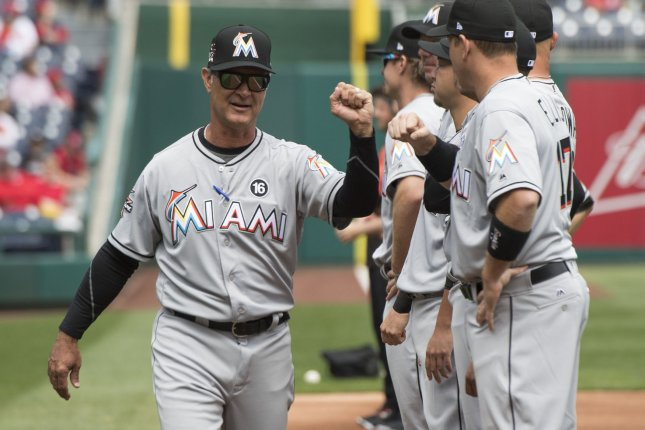 Miami Marlins manager Don Mattingly (8) congratulates his team. File photo by Kevin Dietsch/UPI