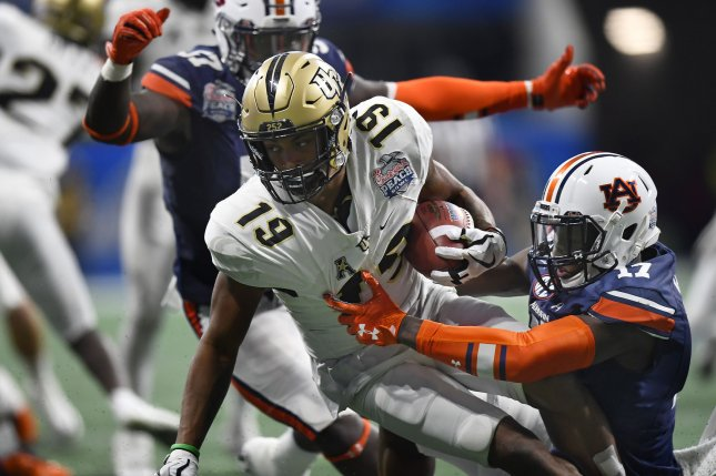 362fc5099 ... kick returner Mike Hughes (19) is tackled by Auburn defenders during  the Chick-fil-A Peach Bowl on January 1