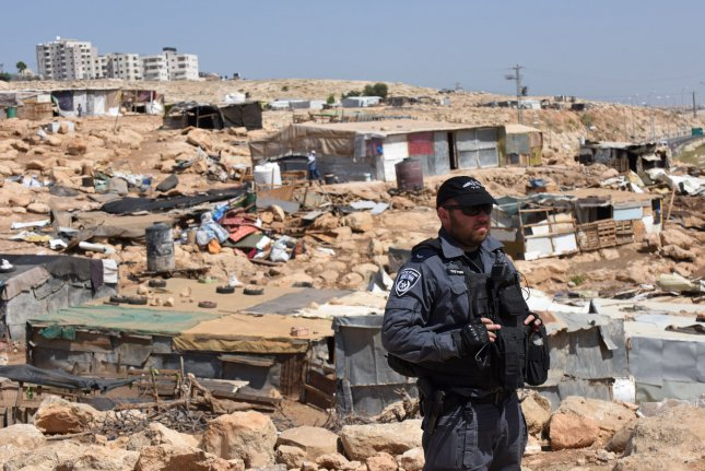 An Israeli police officer stands on a hill overlooking homes demolished by a bulldozer in the West Bank on July 4. The military destroyed ten houses there as part of a plan to relocate Palestinian dwellers. File Photo by Debbie Hill/UPI