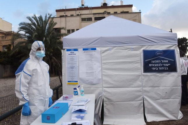 A health worker dons protective gear outside a tent set up for quarantined voters to cast ballots in the national election on March 1, in Tel Aviv, Israel. Photo by Debbie Hill/UPI