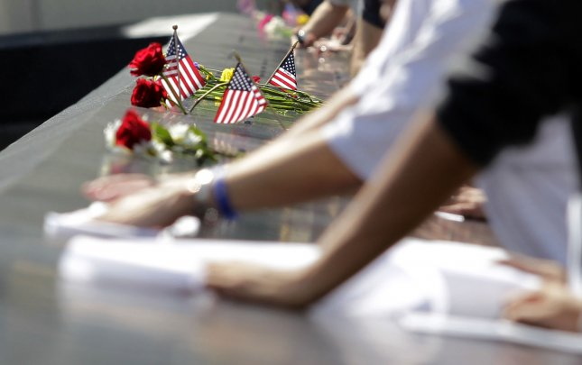 Flags and flowers are placed on the names of the victims of 9/11 that are engraved around the Memorial Pools as visitors make rubbings of them at the opening of the 9/11 Memorial one day after the tenth anniversary of the terrorist attacks on the World Trade Center on 9/11 at Ground Zero in New York City on September 12, 2011. UPI/John Angelillo