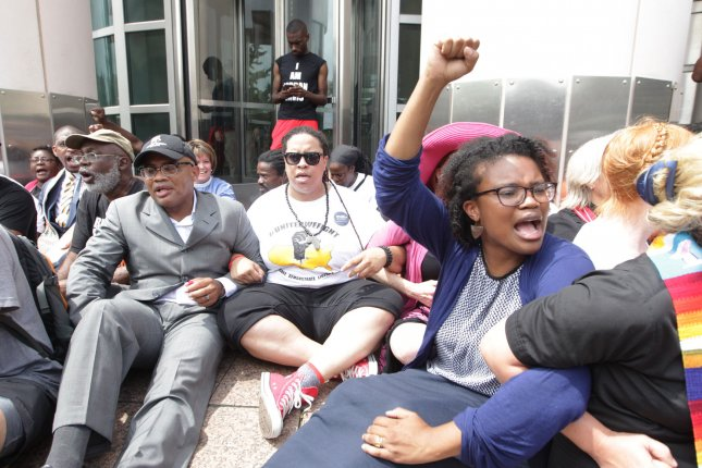 Protesters sit locked in arms in St. Louis on August 10, 2015. They marched to the Federal Building as part of a day of disobedience held during the one-year anniversary of the Michael Brown Jr. shooting death by police in Ferguson, Mo. A Gallup survey shows 61 percent of Americans think racism against blacks is widespread in the United States. File photo by Bill Greenblatt/UPI