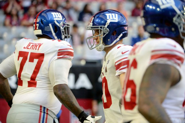 New York Giants' quarterback Drew Eli Manning (C) welcomes other Giants players to the field before the game against the Arizona Cardinals at University of Phoenix Stadium in Glendale, Arizona December 24, 2017. To the left of Manning is Giants left guard John Jerry. Photo by Art Foxall/UPI