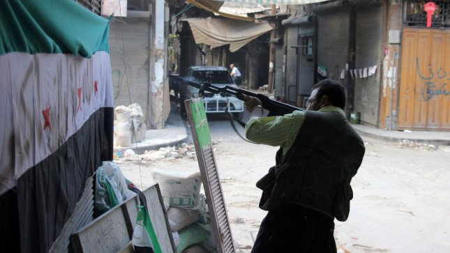 A fighter with the Free Syria Army (FSA) fires his weapon during skirmishes with government forces in the contested neighborhood in the northern city of Aleppo, Syria, September 12, 2012. UPI/Ahmad Deeb