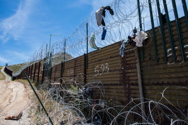 Clothing is seen hanging from barbed wire fencing along the border on June 10 in Tecate, Calif. File Photo by Kevin Dietsch/UPI