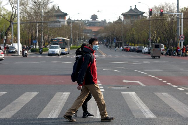 People in China wearing protective face masks walk through an intersection in central Beijing on Thursday. China's capital is slowing returning to normal life from draconian safety measures due to the Covid-19 outbreak, with the government slowly lifting some restrictions on travel and social interactions. Photo by Stephen Shaver/UPI