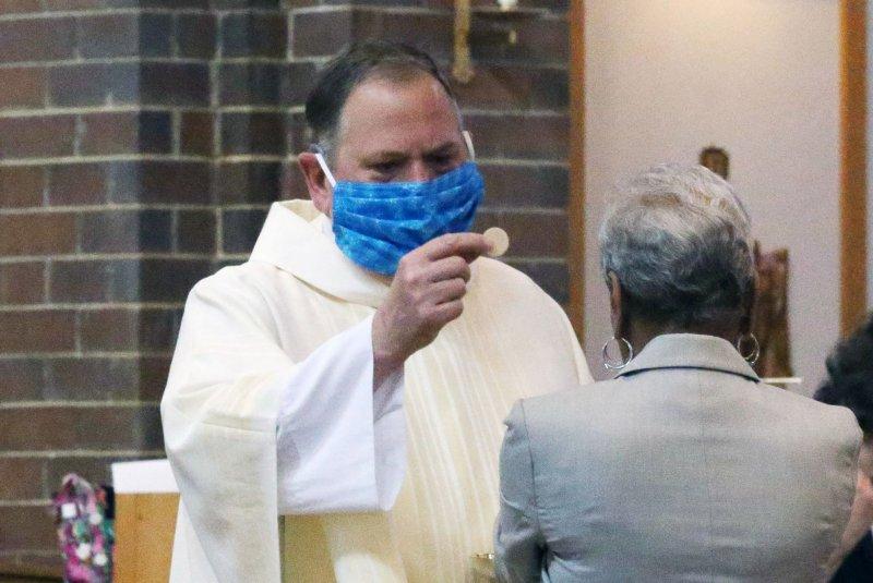 Rev. Bob Evans gives communion to parishioners at the Holy Spirit Catholic Church in Maryland Heights, Missouri. File Photo by Bill Greenblatt/UPI