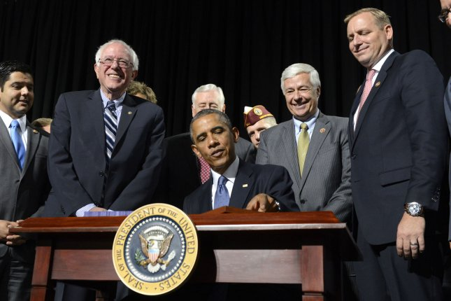 U.S. President Barack Obama, surrounded by congressmen and veteran's officials, signs HR 3230, The Veterans' Access to Care through Choice, Accountability and Transparency Act of 2014, August 7, 2014, at Fort Belvoir, Virginia. The bill aims to improve military veteran's health care by streamlining the VA's bureaucracy in such areas as appointments and training of staff and personnel at VA medical care facilities. UPI/Mike Theiler