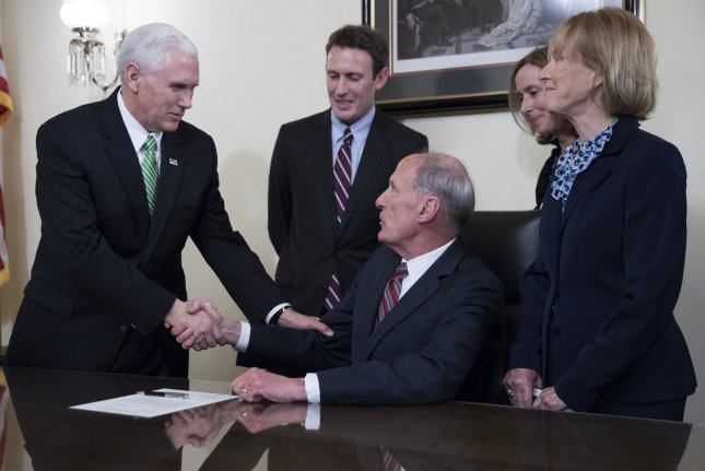 Director of National Intelligence Dan Coats, seated, shakes hands with Vice President Mike Pence during a swearing-in ceremony in the Capitol in Washington on Thursday. Coats is the nation's fifth person to serve in the role, which was created after the Sept. 11 terror attacks. Pool Photo by Shawn Thew/UPI