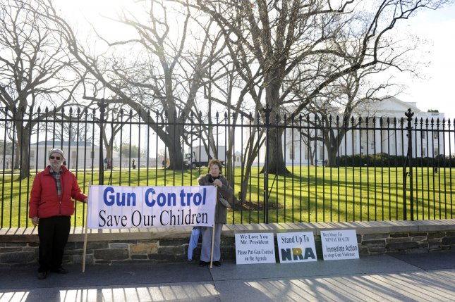 Tom Harvey (L) and his wife Pat Powers, of Rockville, Md., hold a gun control banner in front of the White House Dec. 15 in the aftermath of the shooting rampage at Sandy Hook Elementary School in Newtown, Conn., that left 26 dead, including 20 children. UPI/Mike Theiler