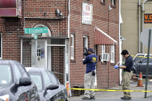 An FBI agent takes photos near where Ahmad Khan Rahami, the suspect in the New York and New Jersey bombings, was apprehended by police on Monday in Elizabeth, N.J. Photo by John Angelillo/UPI