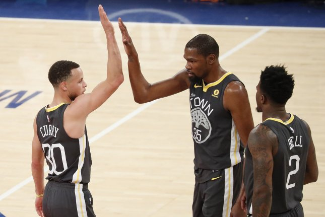 Golden State Warriors' Stephen Curry and Kevin Durant high five after a time out is called in the 3rd quarter against the New York Knicks on Monday at Madison Square Garden in New York City. Photo by John Angelillo/UPI